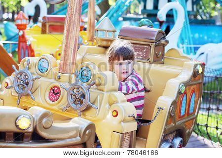 Little Girl Ride On Carousel Pirate Ship In Summer Park