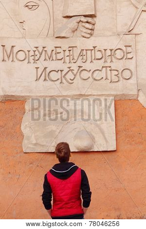 Back Of Man In Red Vest Looking On Embossed Lettering Monumental Art