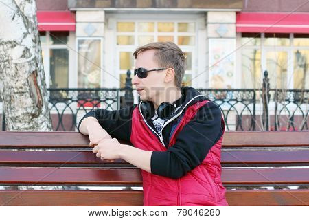 Young Man In Sunglasses And With Headphones Sits On Bench On Street At Spring Day