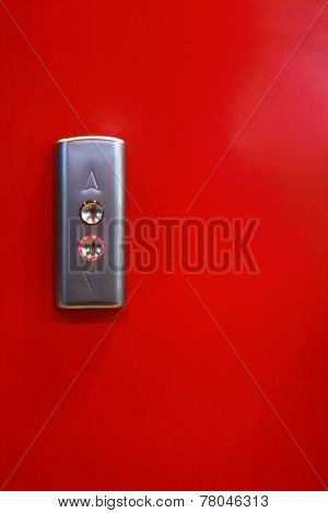 Two Metal Button With Up And Down Arrows Of Lift On Red Wall