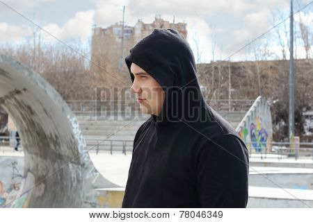 Young Handsome Man In Black Hoodie Stands On Street At Spring Day