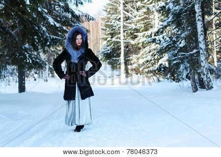 Girl In Fur Coat Stands And Looks Away In Winter Forest