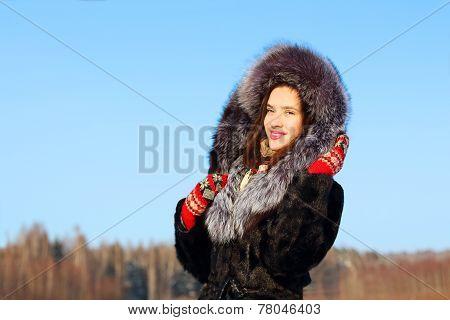 Girl In Fur Coat With Hood Smiles Outdoor In Sunny Winter Day