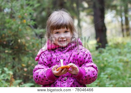 Little Smiling Girl In Pink Holds Mushroom And Looks At Acmera At Autumn Day
