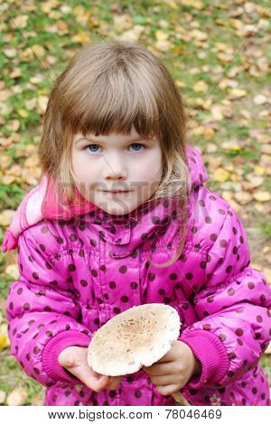 Little Beautiful Girl In Pink Holds Mushroom And Looks At Acmera At Autumn Day
