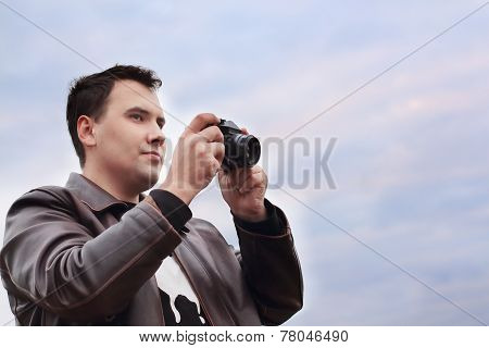 Handsome Smiling Man In Leather Jacket Holds Camera Against Sky