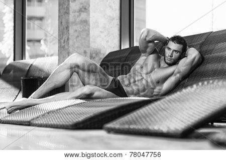 Man Resting On Sun Loungers By Swimming Pool