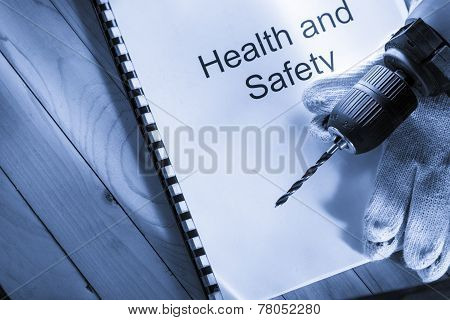 Register With Drill And Gloves On Wooden Background