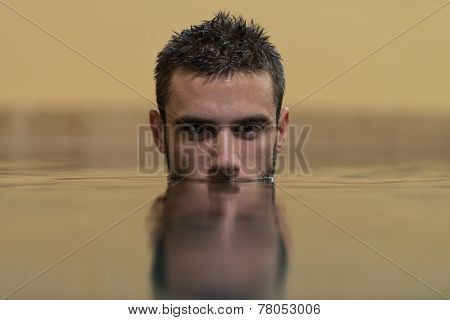 Man Swimming In Pool With Face Half Submerged