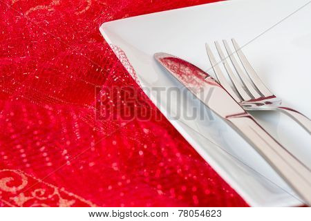 White place setting on red net cloth
