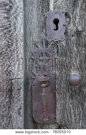 Old run-down wooden door and ornamented iron lock