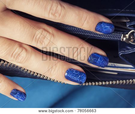 pretty fingers, deep blue manicure close up with purse