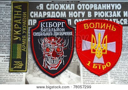 Kiev,Ukraine.Oct 16.Illustrative editorial.Pro-Ukrainian nationalist formations Volyn chevrone .Newspaper with heroic story of soldier as background.At October 16,2014 in Kiev, Ukraine