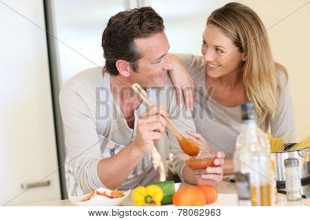 Woman watching husband preparing pasta dish