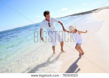 Father and little girl playing together at the beach