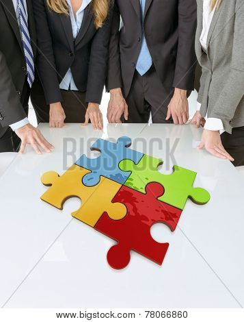 Meeting with people around a table with a four color puzzle