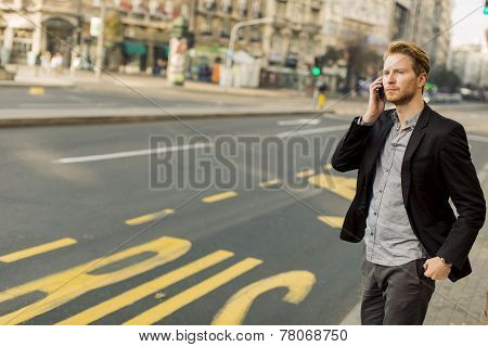Young Man On The Street With Mobile Phone