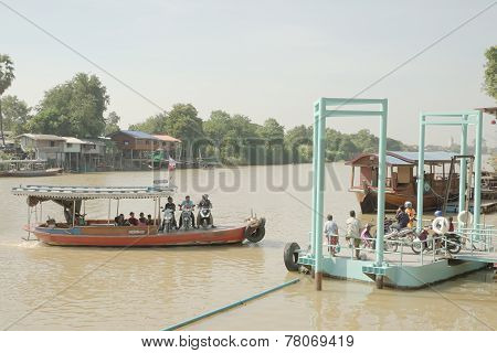 Ferry carrying motorcycle crossing river