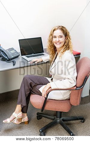 Happy businesswoman sitting at workstation in office with computer