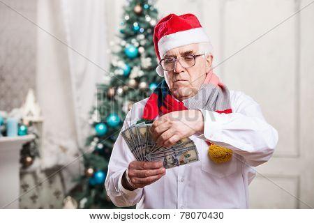 Senior man holding money on Christmas background