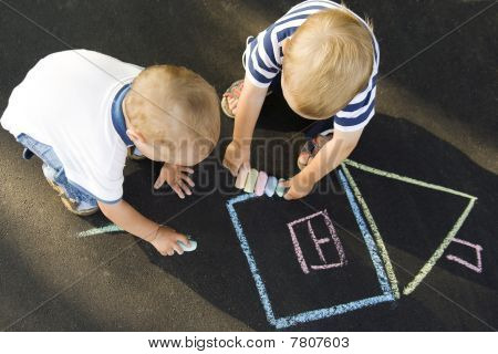 Two Boys Drawing House On Asphalt
