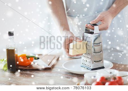 cooking, food, people and home concept - close up of male hands with grater, vegetables and olive oil grating cheese in kitchen