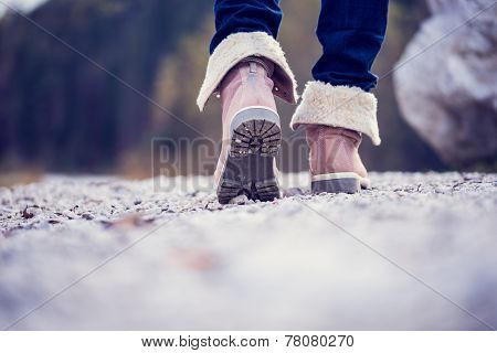 Woman In Boots Walking Along A Rural Path