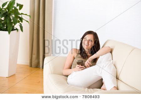 Woman Holding Music Player Listening In Lounge