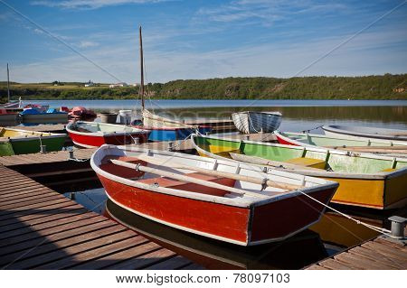 Floating Color Wooden Boats With Paddles In A Lake
