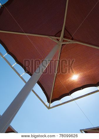 Red Metallic Parasol Beach Umbrella Over Blue Sky