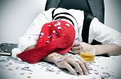 foto of office party  - a man with a santa hat and covered with confetti sleeping in his desk after an office christmas party - JPG