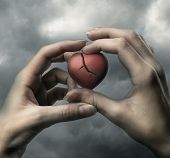 picture of broken heart  - Broken red heart in hands on stormy sky - JPG