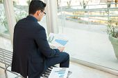 picture of work bench  - Young businessman sitting on a bench while looking at some performance charts at work - JPG