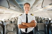 image of cabin crew  - Confident male pilot in uniform keeping arms crossed and smiling while standing inside of the airplane - JPG