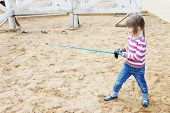 stock photo of rapier  - Pretty little happy girl standing on sand with blue rapier training for fencing - JPG