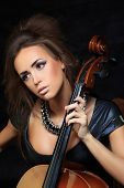 stock photo of cello  - Photo of a beautiful female musician playing a cello - JPG