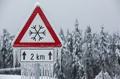 foto of sleet  - Traffic sign for icy road with sleet covered trees - JPG