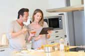 image of 35 to 40 year olds  - Couple in kitchen looking at pasta dish recipe on tablet - JPG