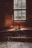 picture of attic  - An old tricycle sits by a window in an attic - JPG