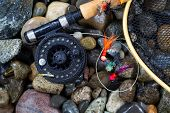 stock photo of fly rod  - Overhead view of fishing fly reel landing net and assorted flies on wet river bed stones  - JPG