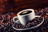 Постер, плакат: Cup of black coffee and spilled coffee beans