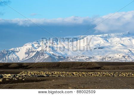 scenic landscape of southern Iceland; of snow-capped mountains, glaciers, grass fields, rivers and lakes formed by the melting ice from the mountains.