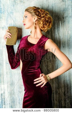Charming young woman wearing elegant evening dress and beautiful hairstyle. Jewellery.  Fashion shot.