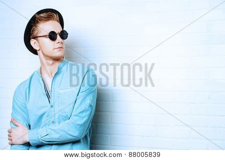 Portrait of a modern young man standing by the brick wall. Beauty, fashion. Hipster style.