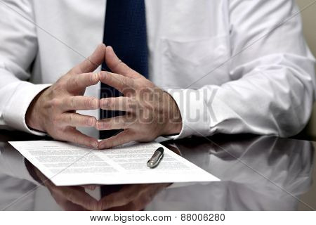 Man with contract or agreement paper with pen wearing white shirt and tie