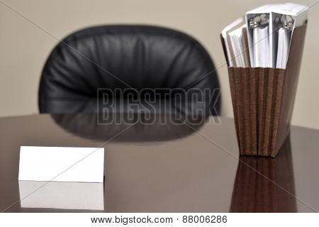 Blank business card on desk for any commercial enterprise with files and chair