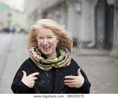 Unexpected snowfall in mid-April, happy portrait of an elderly woman in the street