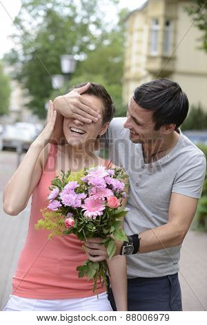 Boyfriend surprising his girlfriend with a  bouquet of flowers