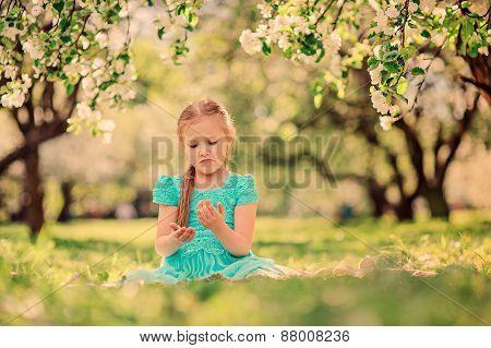 happy kid girl playing in spring blooming apple garden
