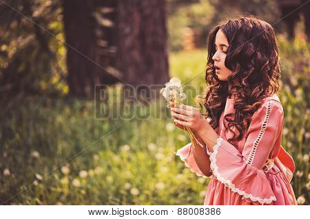 child girl dressed as fairytale princess playing with blow balls in summer forest